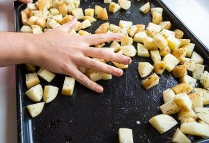 Potato chunks being tossed with olive oil on a baking tray