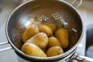 boiled potatoes draining in a colander
