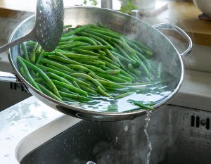 blanched green Beans being drained in a pan