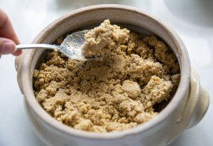 Crumble topping being added to pear and chocolate crumble