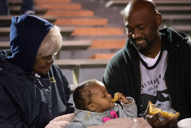Mrs. King, Tanira King (eating nachos) and Terry King keep warm on the visitors' side during the halftime show.
