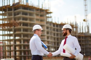 Happy modern architects handshaking on background of building structure