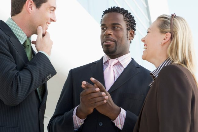Three businesspeople standing outdoors by building talking and s