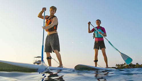 Two paddleboarders learning how to stand-up paddleboard with L.L.Bean stand-up paddleboards and paddling equipment.