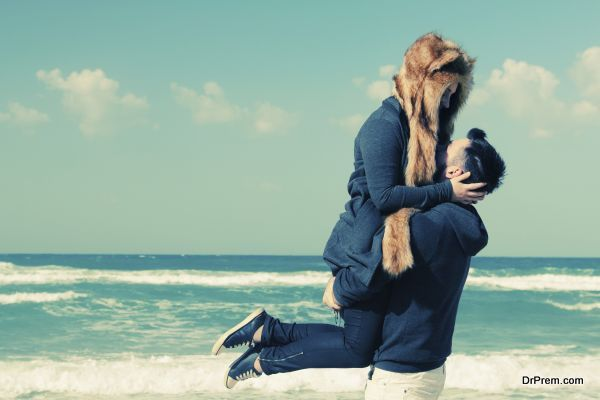 Beautiful young couple relaxing outdoor at winter beach