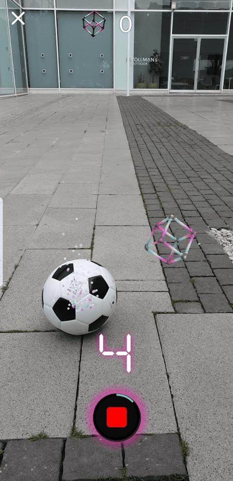 אפליקציית Zooz. התמונה מכילה כדור, קובייה צבעונית וירטואלית במציאות מדומה, ומדרכה ציבורית