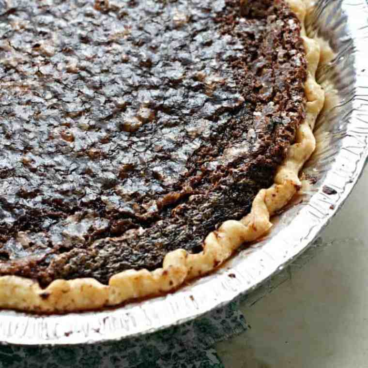 A photo of the chocolate chess pie from overhead showing only one quarter of the pie and showing off the browned edges