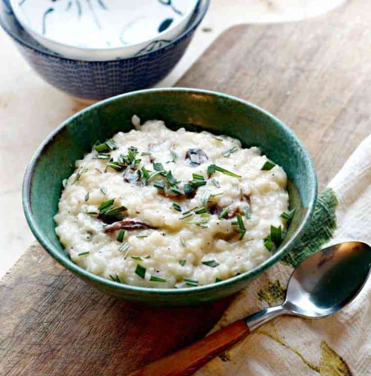 A photo of Creamy No Stir Parmesan Mushroom Risotto at a medium distance with a spoon and two bowls