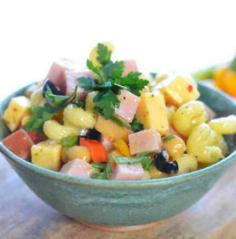 A side view of a green bowl of pasta salad showcasing the parsley, ham, cheese and noodles