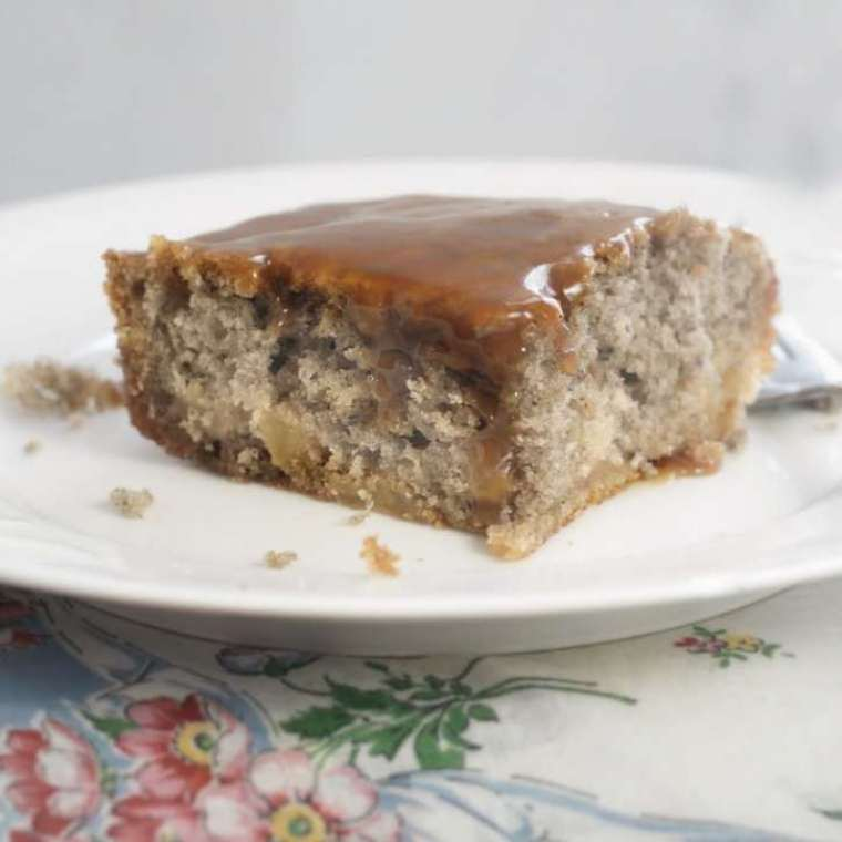 A whole slice of cake sitting with the icing running down the side. Fried Apple Cake with Caramel Icing