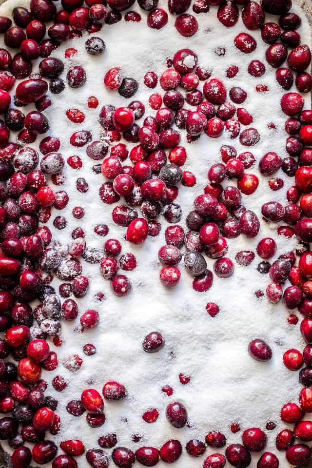 a close up of the white sugar on top of the fresh cranberries