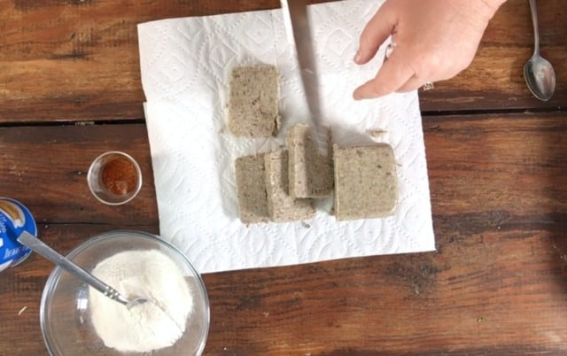 cutting the raw scrapple into slices