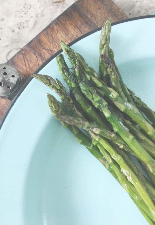 Green asparagus tips on a blue plate with salt shaker