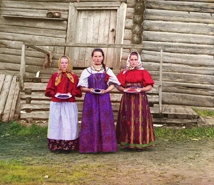 Young Russian peasant women offer berries to visitors to their izba, a traditional wooden house, in a rural area along the Sheksna River near the small town of Kirillov.