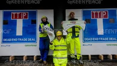 Greenpeace activisten blokkeerden de ingang van het gebouw in Brussel waar de onderhandelingen over het TTIP-akkoord tussen de EU en de VS doorgaan
