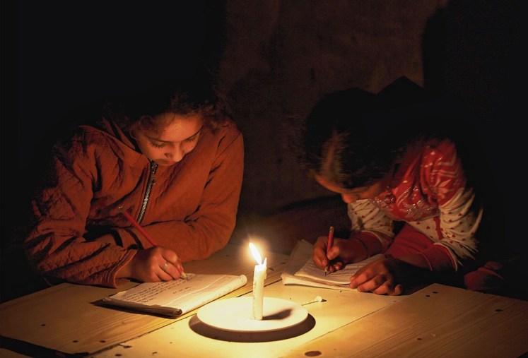 Studeren bij kaarslichtin Palestijns vluchtelingenkamp Khanyounis in de Gazastrook