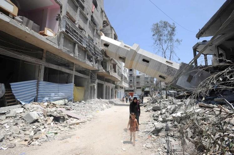 Een Palestijnse moeder en dochter stappen door wat ooit een winkelstraat en een minaret was in Gaza