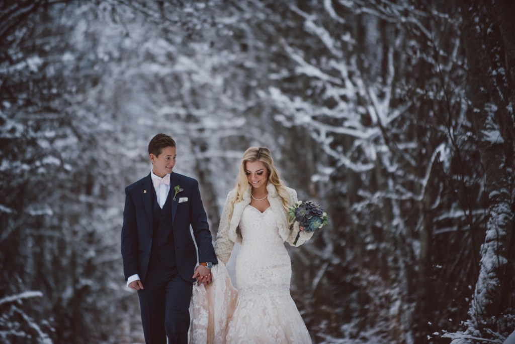 same sex couple holding hands in the winter forest