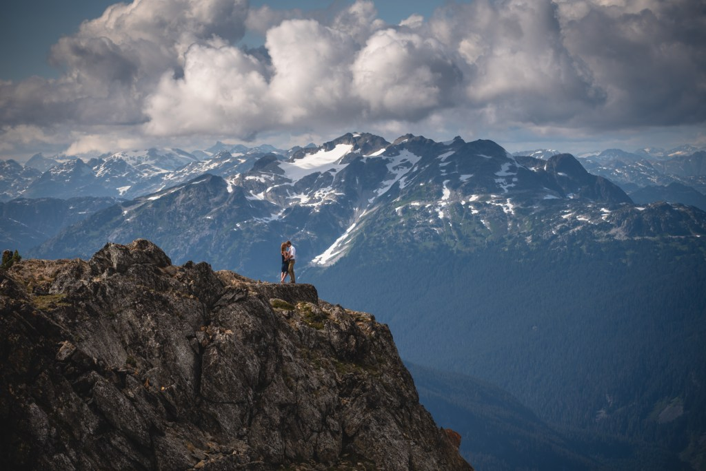 A couple standing on the peak for their Whistler engagement