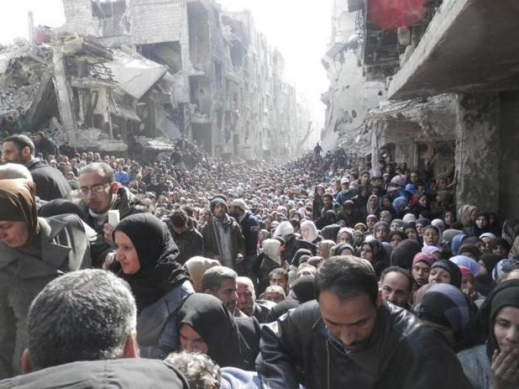 Residents wait to receive food aid distributed by the U.N. Relief and Works Agency (UNRWA) at the besieged al-Yarmouk camp, south of Damascus on January 31, 2014, in this handout picture made available to Reuters February 26, 2014. REUTERS/UNRWA/Handout via Reuters