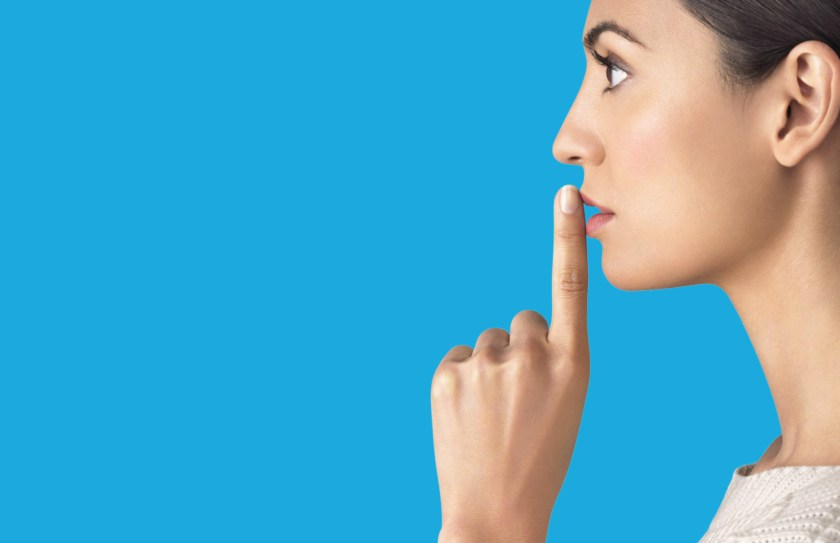 Woman placing finger on mouth to reflect silence