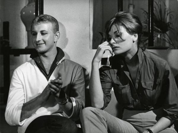 """Scena del film """"La dolce vita"""" - Regia Federico Fellini, 1960 - Piano medio di Gioacchino Stajano e Leontine van Strein, seduti. Lui applaude sorridente. Lei, tiene in mano un bicchiere mezzo pieno, e appoggia il gomito sul ginocchio."""