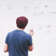 Guy standing in front of a whiteboard with a pen trying to problem solve