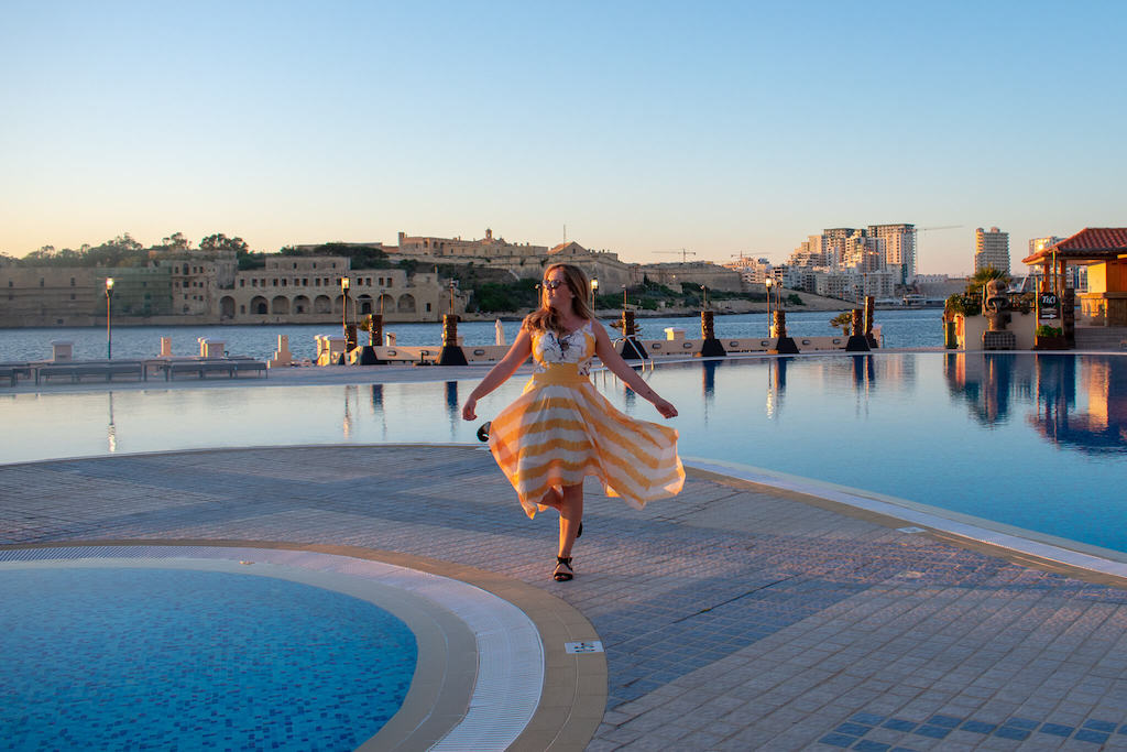 Girl in yellow dress by pool with ocean in background in Malta