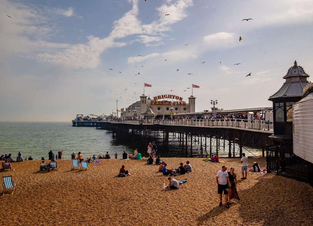 Coastal weekend Trips in the UK, Brighton pier with people on beach and ocean in bakcground