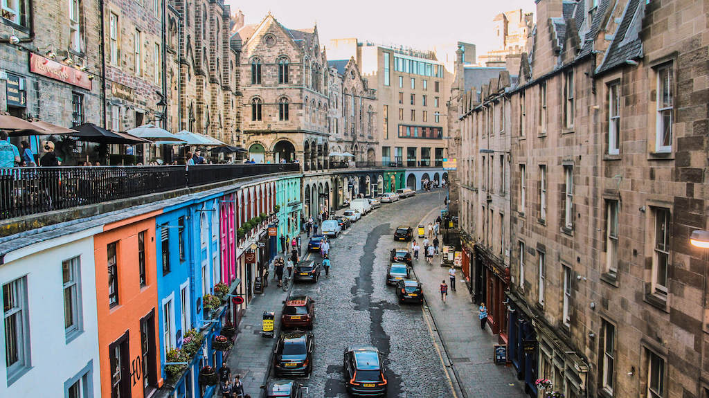 Weekend city breaks in the UK, row of colourful houses below old stone buildings in Edinburgh