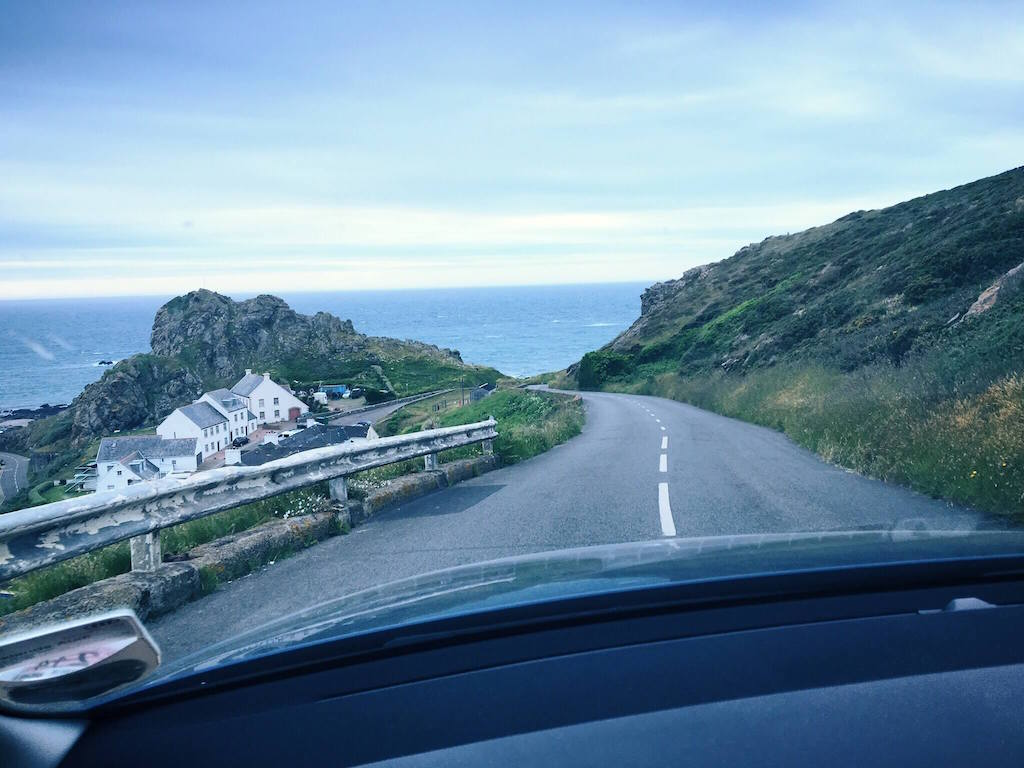 Offshore weekend breaks in the UK, road overlooking cliffs, green scenery and ocean in Jersey
