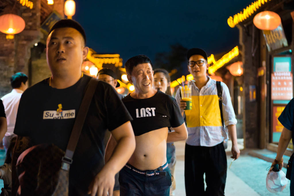 Chinese man with t-shirt rolled up into the Beijing Bikini