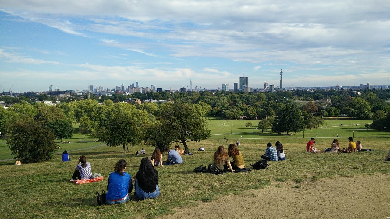People sitting on Primrose Hill overlooking the London Skyline