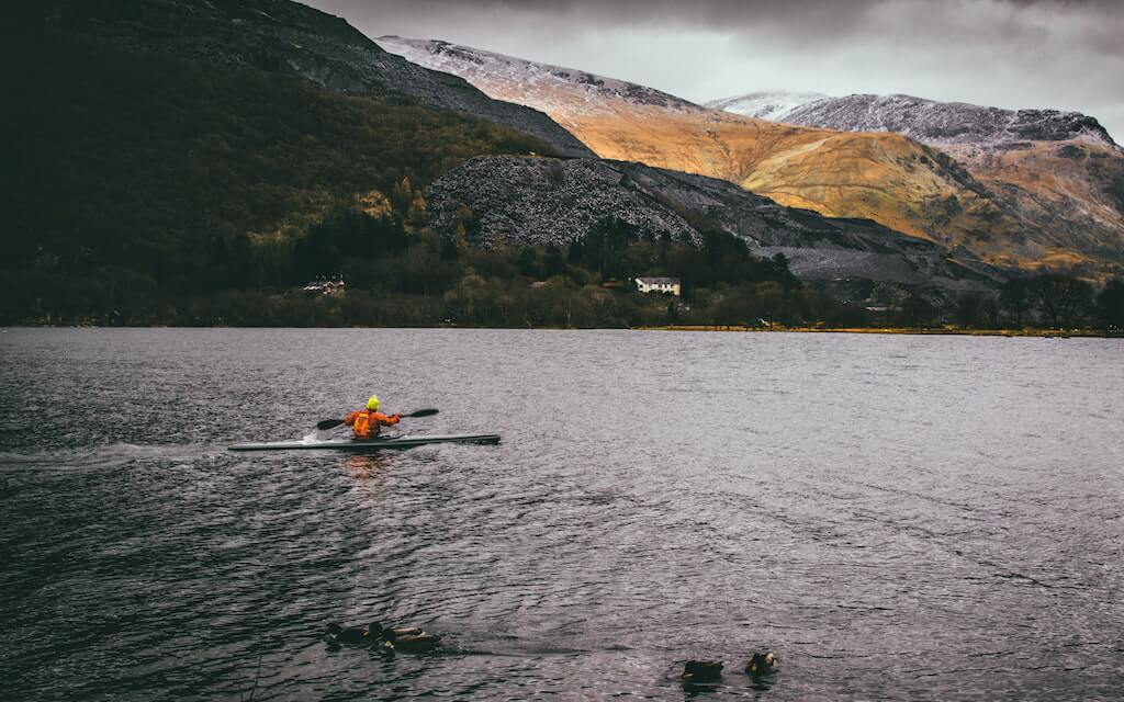 Person kayaking in lake in Llanberis