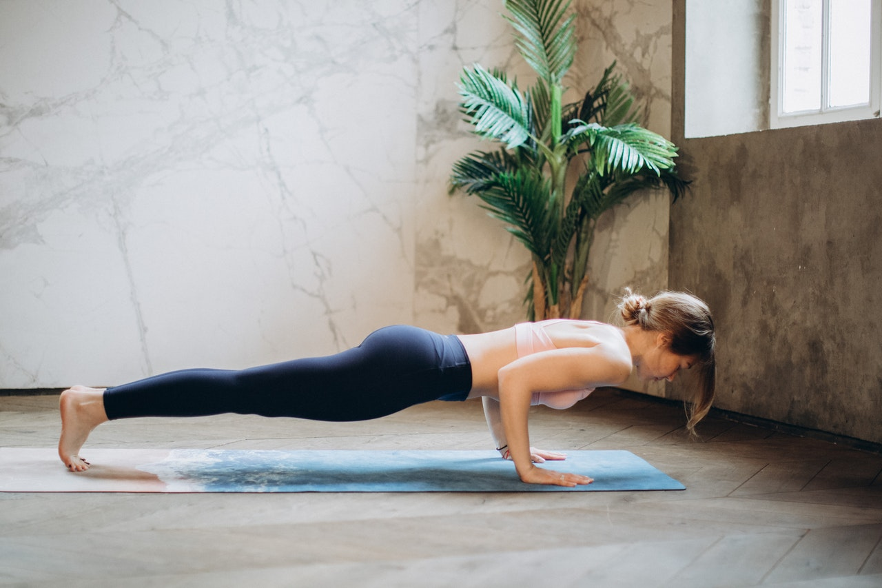 woman-in-black-tank-top-and-black-leggings-doing-yoga