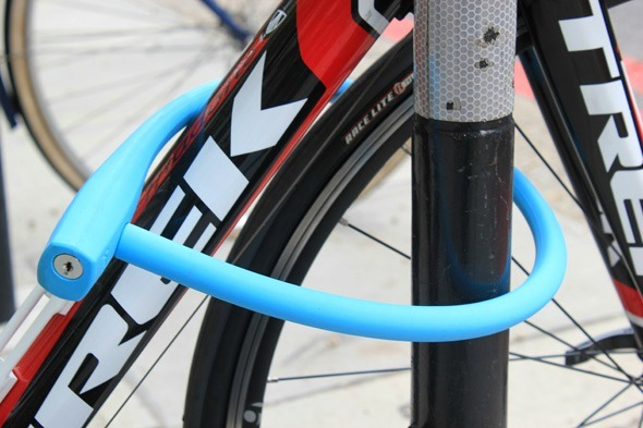 Zoomed in view of the Knog Kabana blue lock showing the keyhole and wrapped around the front wheel of bike as well as frame of Trek Madone