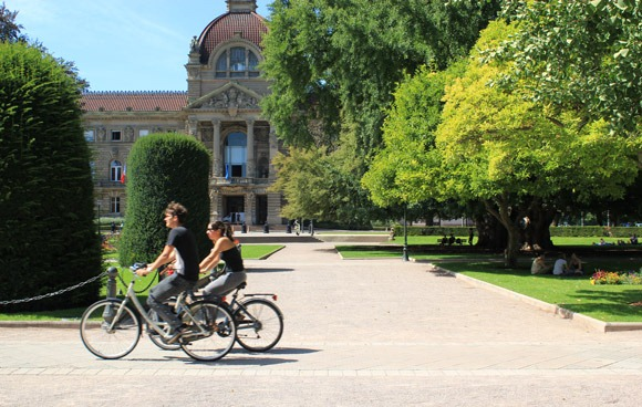 Two cyclists pedal next to the Palais du Rhin