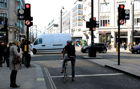 A cyclist waiting patiently at bike lights near Oxford Circus