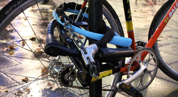7 bike locks around a back wheel and a cycling stand