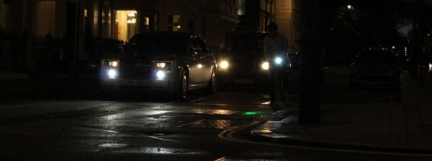 Faint bike light next to cars