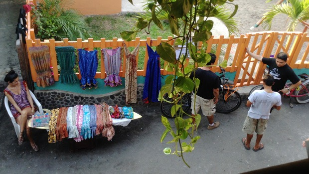 A woman sells clothes next to a bicycle which is for sale
