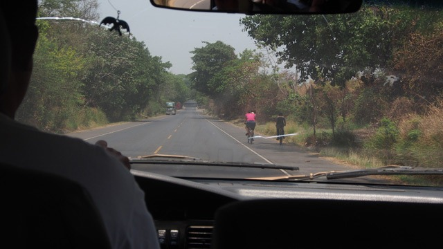 Inside view from a car showing road ahead with two cyclists