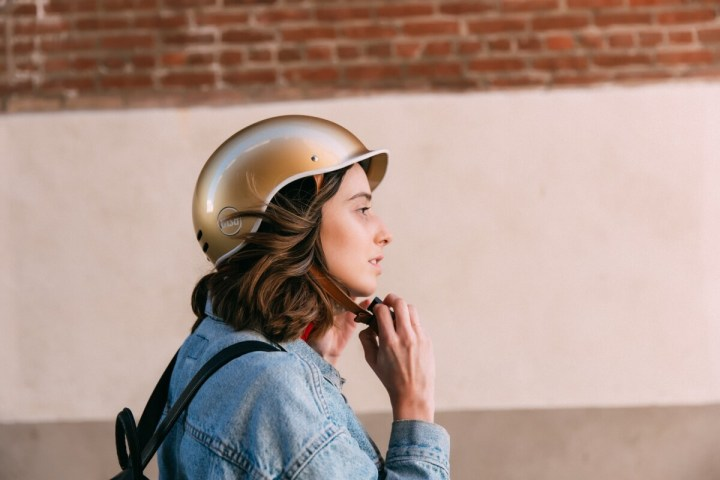 Photograph of woman wearing gold Thousand bike helmet