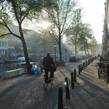 A cyclist rides through a quiet street in Amsterdam