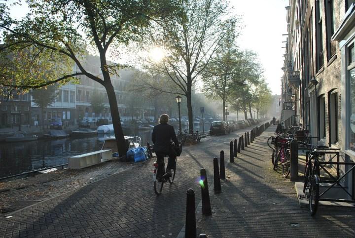 A cyclist rides through a quiet street in Amsterdam