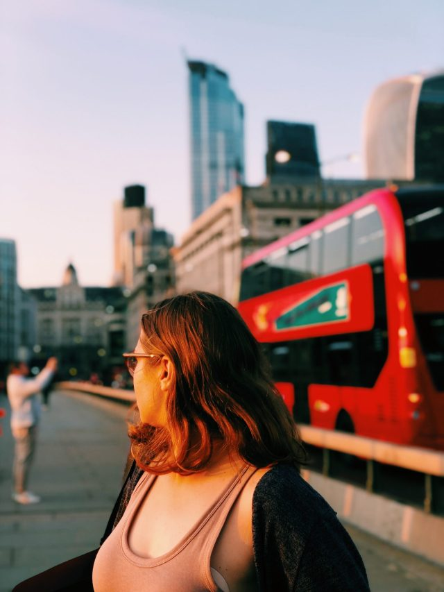 girl on london staycation on london bridge with red bus