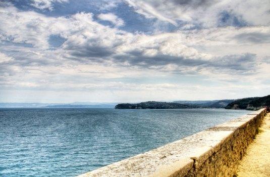 Il mare di Pirano e in lontananza l'Istria vista dal Duomo di San Giorgio. Si notano Izola, Capodistria e in lontananza la costa italiana nei pressi di Trieste (Foto: Caterina Chimenti / Lonely Traveller, licenza CC 2.0)