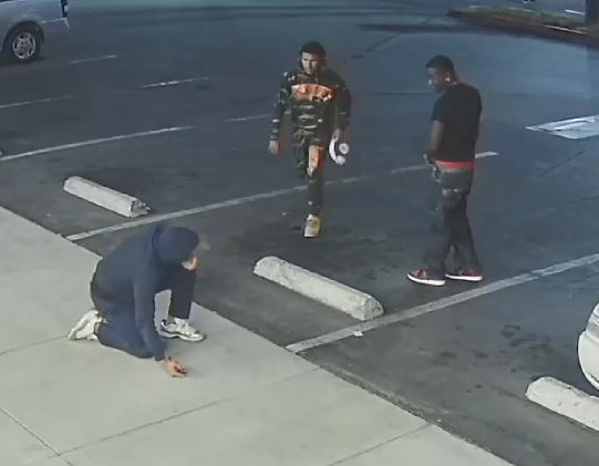 Two robbery suspects walking toward victim