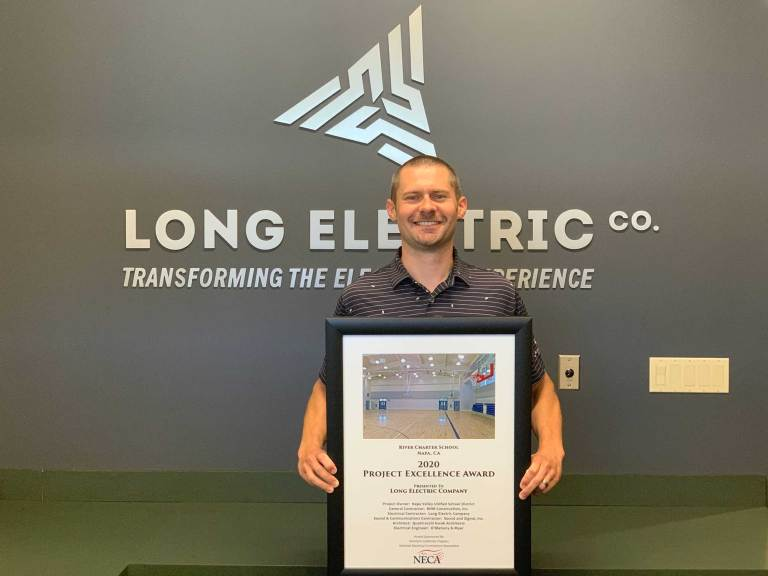 Tom Long holds the award for the 2020 NorCal NECA Project Excellence for work on the River Charter School project