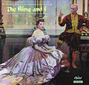 The album cover for Roger and Hammerstein's The King And I, featuring a woman in a large, very formal pink ruffled dress and a man in traditional Thai clothing pointing his finger at the ceiling with a stern look on his face. The lettering bearing the album name is lime green and is Oriental style.